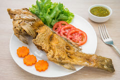 Fried fish with vegetables on plate and sauce Royalty Free Stock Photo