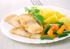 Fried fish with vegetables and potato Stock Photo