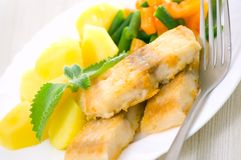 Fried fish with vegetables and potato. For dinner Royalty Free Stock Images
