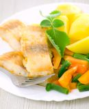 Fried fish with vegetables and potato. For dinner Stock Photos