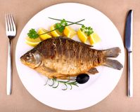 Fried fish on white plate with fork and knife Royalty Free Stock Photo