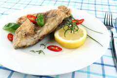 Fried fish on white plate with fork and knife Stock Photo