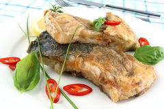 Fried fish on white plate, fork and knife Royalty Free Stock Image