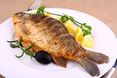 Fried fish on white plate with lemon, fork and knife Royalty Free Stock Image