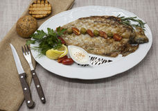 Fried fish whitefish on plate with vegetables and bread with a fork and knife. Royalty Free Stock Image