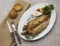 Fried fish whitefish on plate with vegetables and bread with a fork and knife. Royalty Free Stock Photo