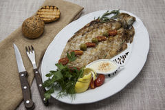Fried fish whitefish on plate with vegetables and bread with a fork and knife. Stock Photography