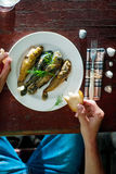 Fried fish. Young man are eating fried fish. Serving table with seashells. top view royalty free stock photography
