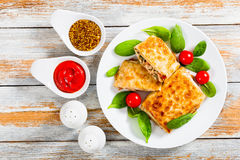 Fried flatbread wraps Stuffed with meat on white dish. With fresh spinach leaves and tomatoes, salt and pepper shakers, ketchup and french mustard in gravy stock photo