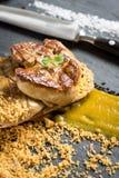 Fried Foie Gras med mangopuré på mörk bakgrund arkivfoto