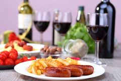 French fries on the dish. Fried french fries and sausages on the dish and food background Stock Image