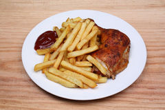 Fried fries and baked chicken leg Royalty Free Stock Image