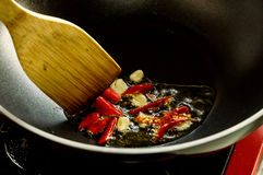 Fried garlic and red chilly in pan stir by wooden spoon. Before cooking spicy food t royalty free stock photography