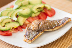 Fried Gilted Sea Beam with tomatoes and avocados. Stock Photo