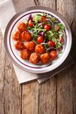 fried glazed meatballs served with salad of lettuce, cherry tomatoes and onions close-up on a plate. Vertical top view royalty free stock photos