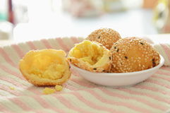 Fried glutinous ball topping sesame stuffed mushed yellow bean on cup. Fried glutinous ball topping sesame stuffed mushed yellow bean on the cup stock images