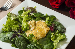 Fried goat cheese salad. Fresh green salad topped with fried goat cheese set on a plate and ready to eat with rose's laying on the table royalty free stock photo