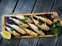Fried goatfish surmullet with lemon on board royalty free stock image