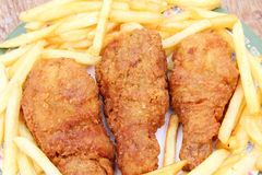 Fried golden chicken legs with french fries Royalty Free Stock Photo