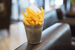 Fried golden French fries is packed into a small metal bucket royalty free stock images