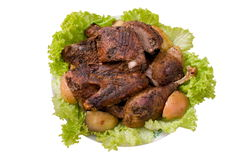 Fried goose. Fried stuffed goose with apples on a plate with greens Royalty Free Stock Images