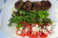 Fried Greek meatballs with tomato, cheese & salad. Meatballs in Greece made with beef and pork stock image