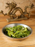 Fried green beans and Chinese antique dragon Royalty Free Stock Photography