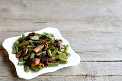 Fried green beans with mushrooms and spices on a plate and on old wooden background with copy place for text Stock Images