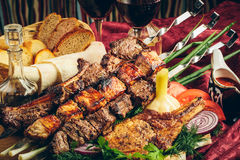 Fried grilled meat with vegetables, sauce and wine Royalty Free Stock Photography