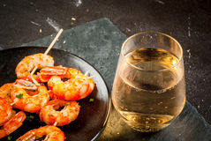 Fried grilled shrimp prawns with white wine. Seafood. Shellfish. Fried grilled shrimp prawns on wooden skewers, with sauce of olive oil and fresh herbs, glass of Royalty Free Stock Photo