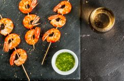 Fried grilled shrimp prawns with white wine. Seafood. Shellfish. Fried grilled shrimp prawns on wooden skewers, with sauce of olive oil and fresh herbs, glass of Royalty Free Stock Image