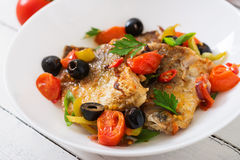 Fried hake fillet with tomato and olives Stock Photo
