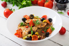 Fried hake fillet with tomato and olives Royalty Free Stock Photo