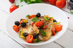 Fried hake fillet with tomato and olives Stock Images