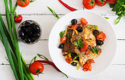 Fried hake fillet with tomato and olives Royalty Free Stock Images