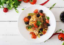 Fried hake fillet with tomato and olives Stock Image