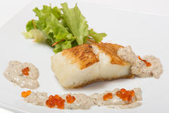 Fried halibut fillet with pepper sauce with salmon caviar Royalty Free Stock Photos