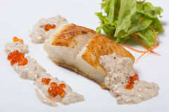 Fried halibut fillet with pepper sauce with salmon caviar. Stock Photo