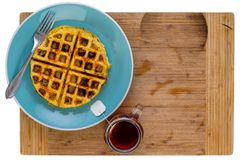 Fried hash brown with honey comb waffle pattern. Golden crispy fried hash brown with honey comb waffle pattern on a blue plate with a teabag steeping in a mug of Stock Image