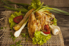 Fried hen in the leaves of lettuce on a board Royalty Free Stock Photos