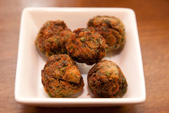 Fried herb balls. Five fried herb balls on a square plate royalty free stock photography