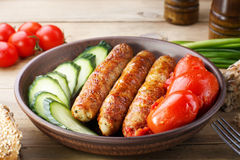 Fried home sausages with fresh cucumber and canned tomatoes. Stock Image