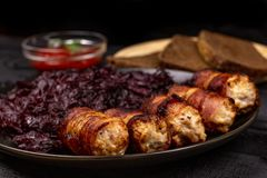 Fried homemade grilled sausages or chevapchichi with stewed sauerkraut, and slices of rye bread and tomato sauce on a wooden royalty free stock image