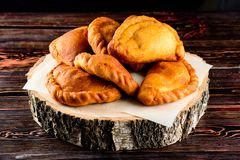 Fried homemade pies on a wooden background in rustic style royalty free stock photo