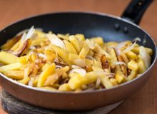 Fried homemade potatoes in a frying pan stock photography