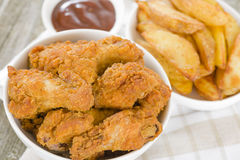 Fried Hot Chicken Wings. Chicken wings dusted in spicy flour and fried until crispy served with potato wedges Royalty Free Stock Photo