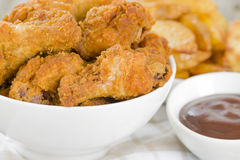 Fried Hot Chicken Wings. Chicken wings dusted in spicy flour and fried until crispy served with potato wedges Royalty Free Stock Images