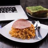 Fried Indonesian Noodle con el jamón y el zumo de naranja Comida mientras que trabaja Imagen de archivo libre de regalías
