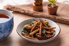 Fried insects - Bamboo worm insect crispy with pandan after frie. D and add a light coating of sauce and garnish Thai pepper powder, tea, brown cloth on wooden Stock Image