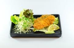 Fried Japanese Salmon i svart maträtt på vit bakgrund Arkivbilder